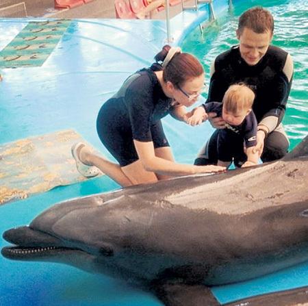 Маленький Сёма, сын Эвелины БЛЁДАНС, в Минском дельфинарии пощекотал бочок умного млекопитающего. Фото: Instagram.com