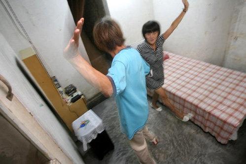 В комнате с бетонными полом и стенами есть кровать, шкаф и трюмо
