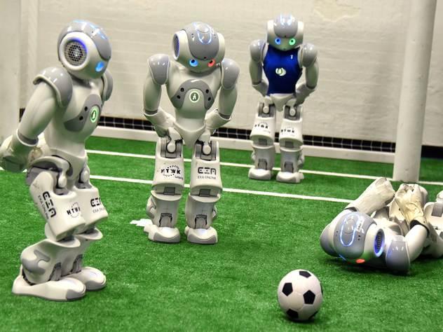 Роботы играют футбол.