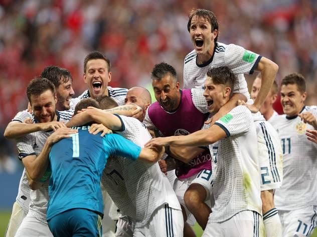 Российские футболисты обнимают вратаря Игоря Акинфеева после победной серии пенальти.